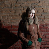 привлекательная девушка зимой возле кирпичной стены — Стоковое фото