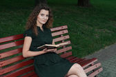 Beautiful young girl in evening reading book outdoor — Foto Stock