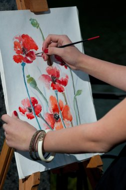 The artist draws a picture on canvas