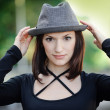The beautiful girl with a hat in the street — Stock Photo