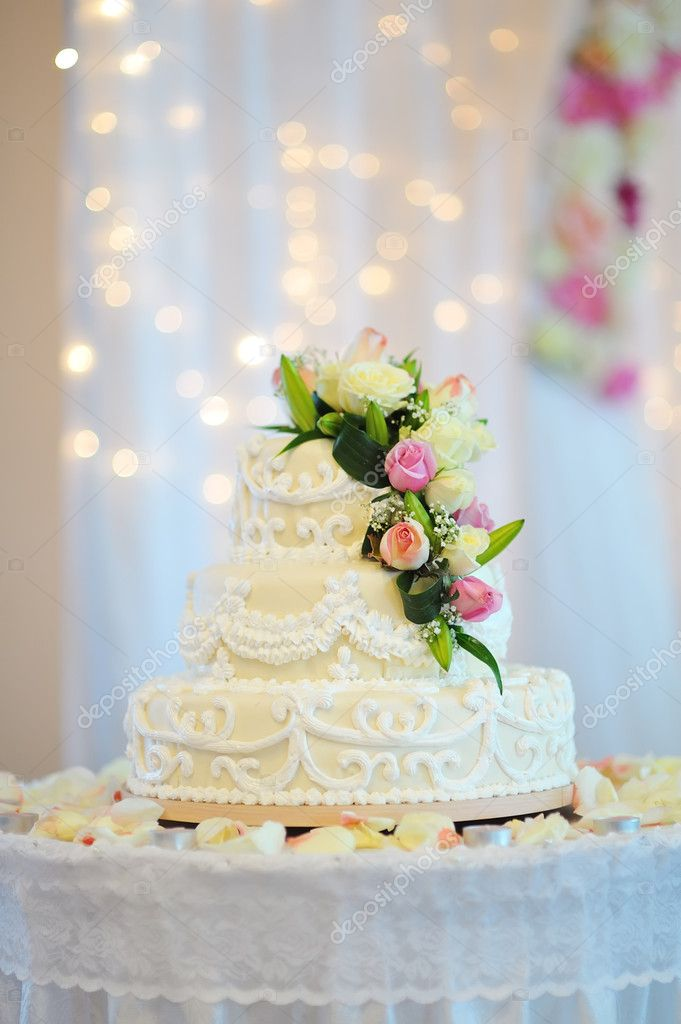 A multi level white wedding cake on a silver base and pink flowers on top — Stock Photo #14291013