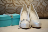 Wedding shoes and earrings bride — Stock Photo