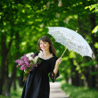 Girl with lilac and openwork umbrella in the park - Stock Photo