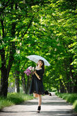 Girl with lilac and openwork umbrella in the park — Stock Photo