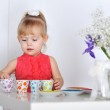 A little girl plays with dishes — Stock Photo #18743413