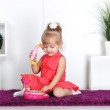 Blonde girl, wearing a dress, talking on the toy phone, calling mom — Stock Photo #18743417