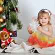 图库照片: Little girl at a Christmas fir-tree