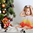 Foto Stock: Little girl at a Christmas fir-tree