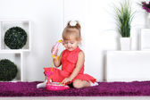 Blonde girl, wearing a dress, talking on the toy phone, calling mom — Stock Photo