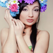 Beautiful young woman with colorful flowers in hair — Stock Photo