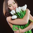 Stock Photo: Girl in green dress with white tulips