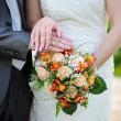Hands and rings on wedding orange bouquet  — Stock Photo