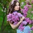 Beautiful girl with a flower lilac — Stock Photo #25053655