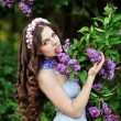 Beautiful girl with a flower lilac — Stock Photo #25053683