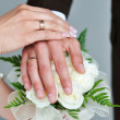 Hands and rings on wedding bouquet — Stock Photo #26144225