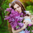 Beautiful girl with a flower lilac the sun — Stock Photo