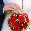 Hands and rings on wedding bouquet — Stock Photo #26327109