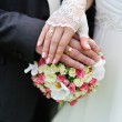 Hands and rings on wedding bouquet — Stock Photo #26581063