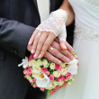 Hands and rings on wedding bouquet — Stock Photo #26794959