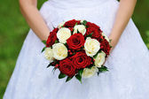 Red and white wedding bouquet of roses in the hands of the bride — Stock Photo