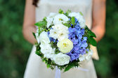 Beautiful wedding bouquet in hands of the bride — Stock Photo