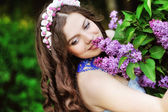 Beautiful girl and blossoming lilac trees — Stock Photo