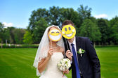 Bride and groom with paper smileys — Stock Photo