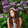 Beautiful young woman in lilac flowers, outdoors portrait — Stock Photo