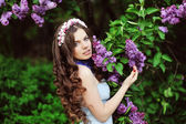 Beautiful young woman in lilac flowers, outdoors portrait — Стоковое фото