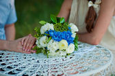 Groom's hands and wedding bouquet on a table — Stok fotoğraf