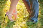 Bride and groom stay on green grass — Stock Photo