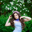 Beautiful young brunette womstanding on trees background — Stock fotografie #28780645