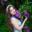 Beautiful girl with a flower lilac — Stock Photo
