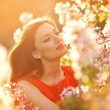 Stock Photo: Portrait beautiful girl on background blooming tree
