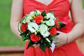 Bride in red dress holding wedding bouquet — Stock fotografie