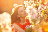 Portrait beautiful girl on background blooming tree — Stock Photo