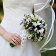 Beautiful wedding bouquet at bride's hands — Stock Photo