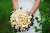 Beautiful wedding bouquet at bride's hands — Stock Photo
