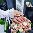 Hands and rings on wedding bouquet — Stock Photo #29304695