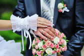 Hands and rings on wedding bouquet — 图库照片
