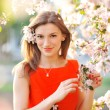 Beautiful woman with white flowering tree — Stock Photo