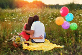Man and woman sitting in the field and colorful balloons — Stock Photo