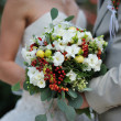 Bride holding wedding bouquet with white flowers — Stock Photo