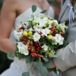 Stock Photo: Bride holding wedding bouquet with white flowers