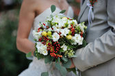 Bride holding wedding bouquet with white flowers — Stok fotoğraf