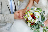 Groom and bride holding hands with wedding rings — Stock Photo