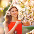 Beautiful young girl in the park and a flowering tree — Stock Photo