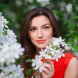 Beautiful young girl in the park and a blossoming white tree — ストック写真