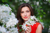 Beautiful young girl in the park and a blossoming white tree — Stock Photo