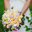 Bride holding white wedding bouquet of roses and love flower — Stock Photo